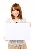 Mujer de negocios asiática joven que sostiene la boa blanca vacía Imagen de archivo