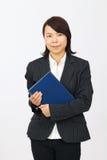 Mujer de negocios asiática joven que sostiene un libro Imagen de archivo libre de regalías