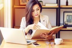 Mujer de negocios asiática joven que trabaja en el lugar de trabajo imagen de archivo