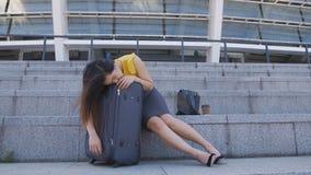 Mujer de negocios asiática que duerme en la maleta al aire libre almacen de video