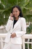 Mujer de negocios asiática que ríe con el teléfono celular Imagen de archivo libre de regalías