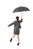 Mujer de negocios asiática que salta con el paraguas Foto de archivo