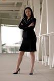 Mujer de negocios asiática que se coloca con parecer plegable brazos serio foto de archivo