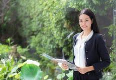 Mujer de negocios asiática que sostiene la carpeta del tablero en la oficina Imagen de archivo libre de regalías