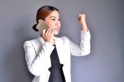 Mujer de negocios asiática que sostiene un teléfono móvil con éxito Foto de archivo libre de regalías