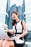 Mujer de negocios asiática que trabaja afuera en el ordenador foto de archivo libre de regalías