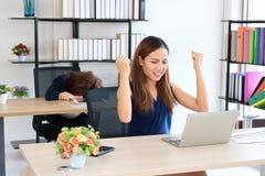Mujer de negocios asi?tica acertada que aumenta las manos con la curva del colega del competidor abajo de la cabeza en el escrito fotografía de archivo libre de regalías