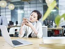 Mujer de negocios asiática joven que juega con el teléfono móvil en oficina Foto de archivo