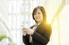 Mujer de negocios asiática joven que manda un SMS en smartphone Fotos de archivo libres de regalías