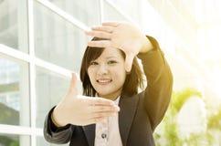 Mujer de negocios asiática que hace el marco de la mano Foto de archivo libre de regalías