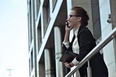 Mujer de negocios atractiva del éxito que sonríe y que habla en smartphone Fotos de archivo libres de regalías