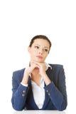 Mujer de negocios atractiva proping su cabeza, sentándose. Imagen de archivo libre de regalías