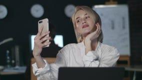 Mujer de negocios atractiva que hace el selfie en el teléfono móvil en oficina oscura metrajes