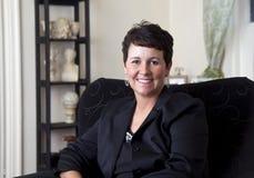 Mujer de negocios atractiva que se relaja y que sonríe Foto de archivo libre de regalías