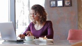 Mujer de negocios atractiva que se sienta en un café almacen de video