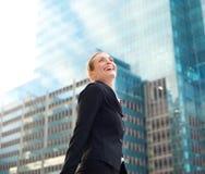 Mujer de negocios atractiva que sonríe y que camina en la ciudad Fotos de archivo libres de regalías