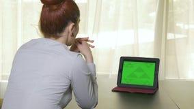 Mujer de negocios atractiva que tiene una videoconferencia de la PC de la tableta almacen de video