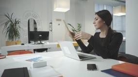 Mujer de negocios atractiva que trabaja en la oficina y que mira el marco de la foto metrajes