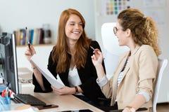Mujer de negocios bastante joven dos que habla y papeles de repaso en la oficina fotografía de archivo