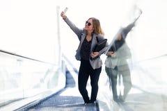 Mujer de negocios bastante joven que toma un selfie con el teléfono móvil en las escaleras mecánicas Fotografía de archivo