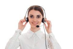 Mujer de negocios bonita joven en uniforme con los auriculares y el micrófono que miran la cámara aislada en el fondo blanco Imagen de archivo libre de regalías