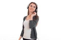 Mujer de negocios bonita joven en uniforme con los auriculares y el micrófono que parecen ausentes y sonrisa aislada en blanco Imagen de archivo