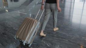 Mujer de negocios bonita joven que camina en el aeropuerto con su equipaje mientras que espera su cola el registro, viajando almacen de video