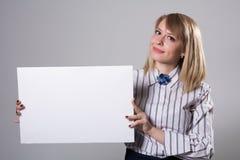 Mujer de negocios bonita que lleva a cabo una muestra en blanco Fotografía de archivo libre de regalías