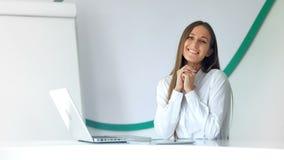 Mujer de negocios bonita sonriente que se sienta en oficina ligera moderna metrajes