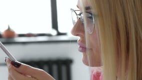 Mujer de negocios brasileña que habla en el teléfono móvil usando el equipo creativo de la nota de voz de la grabación de la inte almacen de metraje de vídeo
