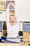 Mujer de negocios cansada que bosteza en oficina foto de archivo libre de regalías
