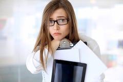 Mujer de negocios cansada que se coloca en la oficina imagenes de archivo