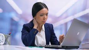 Mujer de negocios cansada que sufre del dolor de cuello que sienta el ordenador portátil delantero, atención sanitaria almacen de video