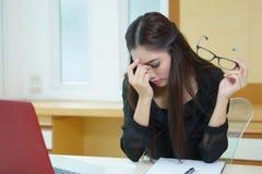 Mujer de negocios cansada que tiene dolor de cabeza mientras que trabaja en el escritorio Imágenes de archivo libres de regalías