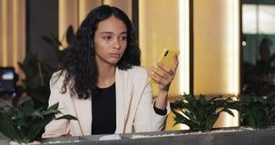 Mujer de negocios cansada usando smartphone en café Muchacha que se sienta en café coworking y de consumición moderno metrajes