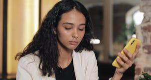 Mujer de negocios cansada usando smartphone en café Muchacha que se sienta en coworking y drinkin modernos almacen de video