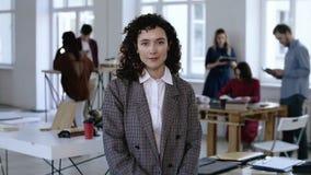 Mujer de negocios caucásica joven en la ropa formal que toca su pelo rizado con mirada enfocada seria en la oficina moderna almacen de video