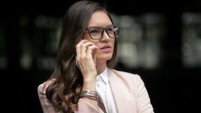 Mujer de negocios caucásica joven que habla en el teléfono y que mira el vigilar fondo urbano del edificio de la ciudad metrajes