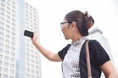 Mujer de negocios china que toma la foto con su teléfono elegante Foto de archivo libre de regalías