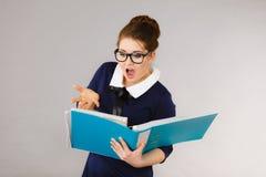 Mujer de negocios chocada que mira documentos Foto de archivo libre de regalías
