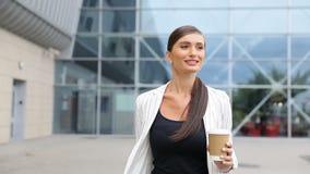 Mujer de negocios con café y la maleta que camina cerca de aeropuerto almacen de video