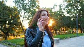 Mujer de negocios con cierre del smartphone para arriba en parque del otoño en luz de la puesta del sol La muchacha tiene convers almacen de metraje de vídeo