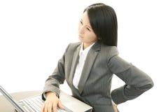 Mujer de negocios con dolor de espalda Foto de archivo libre de regalías