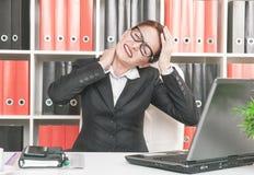 Mujer de negocios con dolor en su cuello y cabeza Foto de archivo