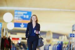 Mujer de negocios con el documento de embarque y pasaporte en aeropuerto internacional Fotografía de archivo libre de regalías