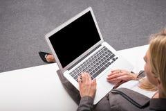 Mujer de negocios con el ordenador en su revestimiento imagen de archivo libre de regalías