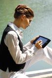 Mujer de negocios con el ordenador portátil en el mar Imagen de archivo