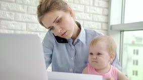 Mujer de negocios con el teléfono de discurso del bebé Funcionamiento de la madre del negocio almacen de metraje de vídeo