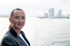 Mujer de negocios con la cara pecosa en la chaqueta que presenta en el mar Imagen de archivo