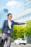 Mujer de negocios con la cartera en taxi de cogida del distrito de oficina Fotografía de archivo libre de regalías